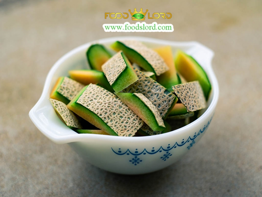 A closeup of a sliced pile of melon fruit in a bowl