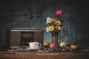 Still life with vases, flowers, fruit, coffee cups and a retro radio receiver.