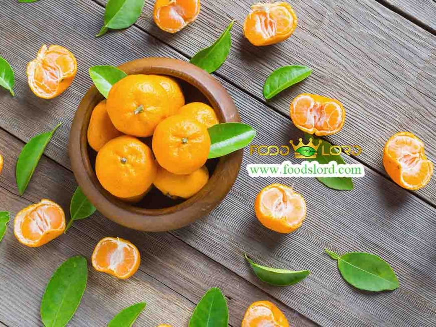 fresh mandarins in wooden bowl with leafs on old wooden table